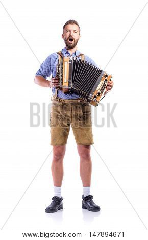 Handsome young man in traditional bavarian clothes playing accordion and singing. Oktoberfest. Studio shot on white background, isolated.