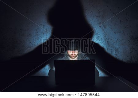 Hacker works in dark empty room. His shadow is on the wall