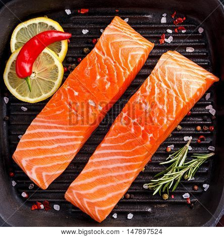 Fresh raw salmon fillet with lemon, herbs and spices