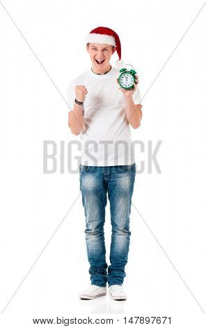 Caucasian young man wearing christmas hat for santa. Teenager in white t-shirt with alarm clock isolated on white background. Successful boy wearing Santa Claus hat - full lenght portrait.