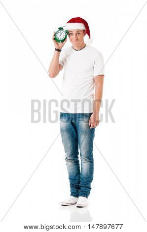 Caucasian young man wearing christmas hat for santa. Teenager in white t-shirt with alarm clock isolated on white background. Happy boy wearing Santa Claus hat - full lenght portrait.