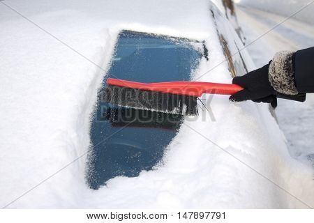Woman's hand in black garment brushing snow from car windshield closeup