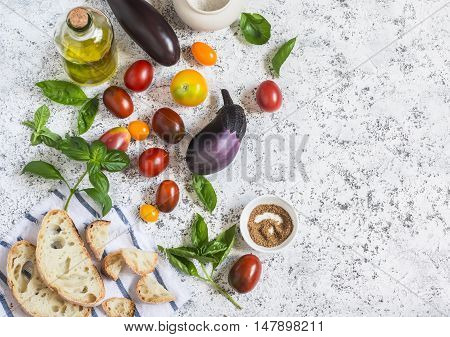 Ingredients for the panzanella salad - eggplant tomatoes ciabatta bread olive oil and basil. On a light background top view