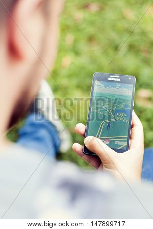 Bucharest, ROMANIA - August 20 2016: Young man playing Pokemon Go on his mobile phone in the park. BUCHAREST -August 20 2016