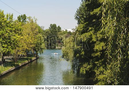 Bucharest, ROMANIA - August 21 2016: View of Alexandru Ioan Cuza park or IOR park on a Sunday afternoon. People on a boat on the lake. BUCHAREST -August 21 2016