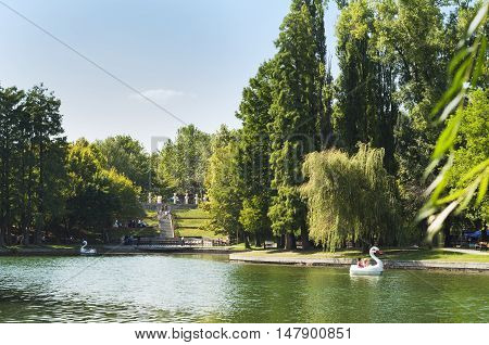 Bucharest, ROMANIA - August 21 2016: View of Alexandru Ioan Cuza park or IOR park on a peaceful Sunday afternoon. People on boats or strolling through the park. BUCHAREST -August 21 2016