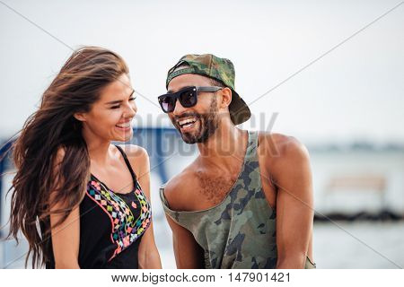 Portrait of romantic young beautiful couple in love laughing at the sea pier