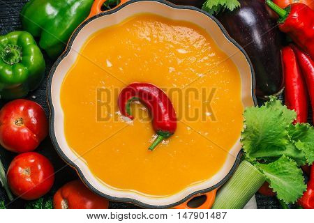 Orange pumpkin puree in the iron pan in the form of pumpkin among various fresh vegetables on the table