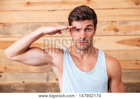Serious young man standing and saluting over wooden background