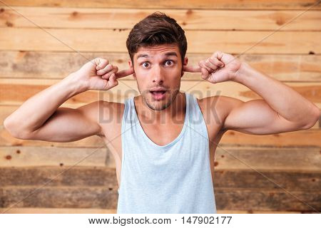 Handsome young man closed ears by fingers over wooden background