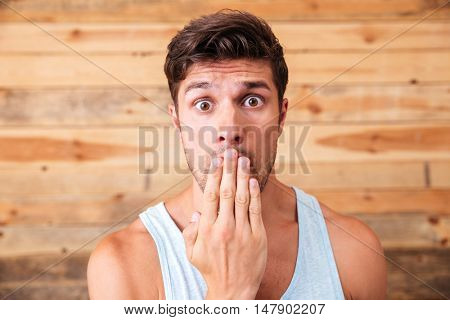Closeup of shocked young man covered his mouth by hand over wooden background