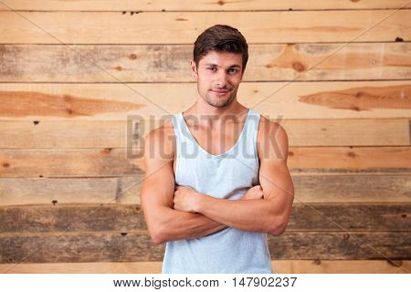 Smiling confident young man standing with arms crossed over wooden background