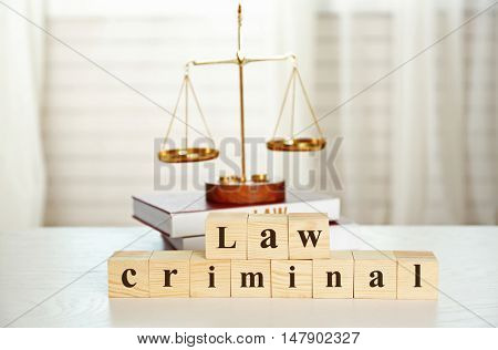Wooden cubes with phrase LAW CRIMINAL and scales on a table