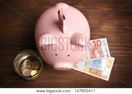 Pink piggy bank, glass of water and euros on wooden background. Saving water concept