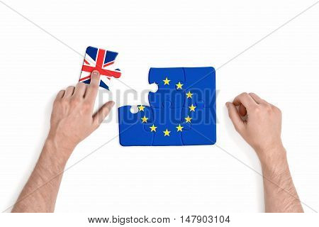 Hand holding piece of jigsaw puzzle with flag of European Union and Great Britain isolated on white background. Brexit puzzle concept. British withdrawal. Significant decision.