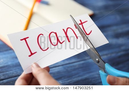 Hand cutting phrase I CAN'T on blue wooden background