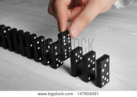 Male hand getting out domino from row on wooden table
