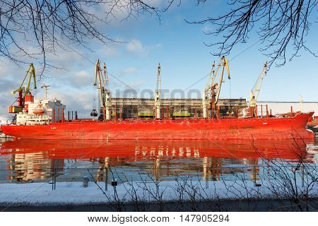 A big cargo ship reflecting on a river
