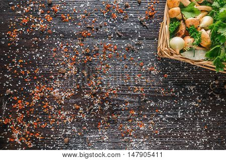 Fresh bovines mushrooms and spices in the wicker tray on the dark wood surface
