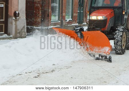 A tractor cleaning snow from the street
