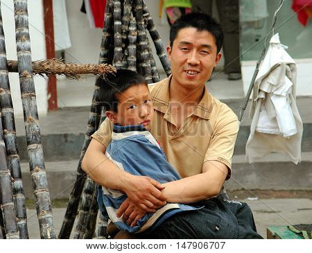 Huang Long Xi China - April 27 2005: Chinese father holding his young son selling stalks of sweet sugar cane on the street