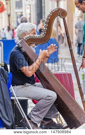 Quebec City, Canada - July 27, 2014: Older man playing a harp on downtown street.