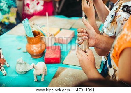 children's hands sculpts clay crafts pottery school