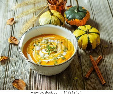 Roasted pumpkin soup with cream and pumpkin seeds on wooden background. Selective focus. Toning, filter.