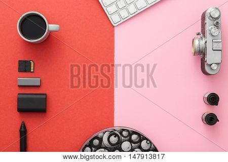 Work space on red table of a creative designer or photographer with laptop tablet camera and other objects of inspiration and copy space. Stylish home studio concept of technology trends. View from above.