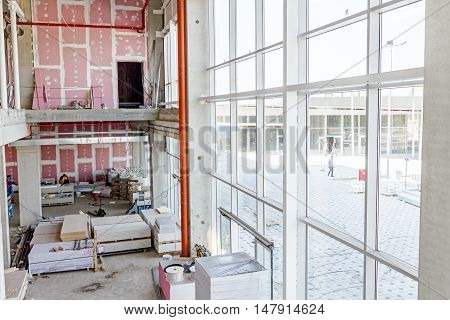 View on indoor construction site of unfinished modern large showroom with gypsum wall and huge windows.
