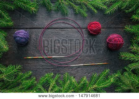 Frame of evergreen branches, colorful wool balls and knitting needles on the dark wood surface
