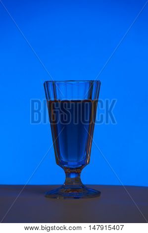 Crystal glass with a drink on a blue background