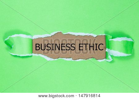 business ethic message written under torn green paper