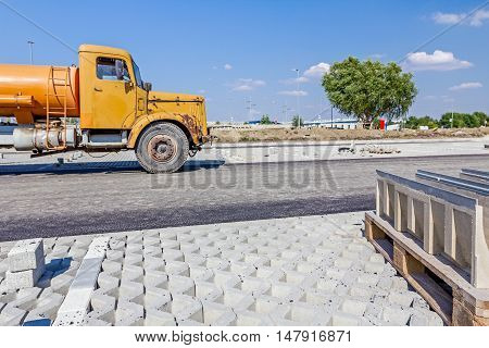 Yellow vintage tank truck is parked on building site. Landscape transform into urban area.