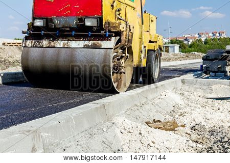 Small steamroller is flatting new road made of asphalt. Detail on newly installed curb. Close up view on roadside.