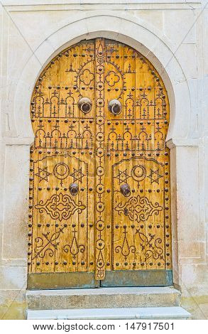 The traditional arabic door decorated with islamic patterns made of rivets Tunis Tunisia.