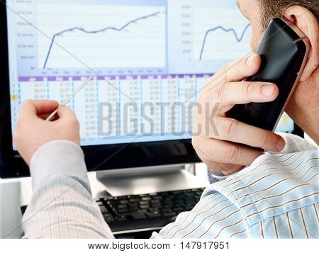 Man on a Phone Analyzing Financial Data and Charts on Computer Screen