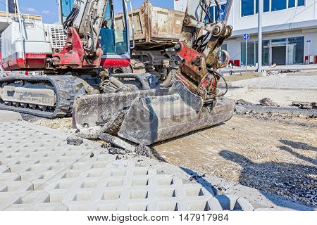 Small excavator removes broken asphalt and gravel on construction site.
