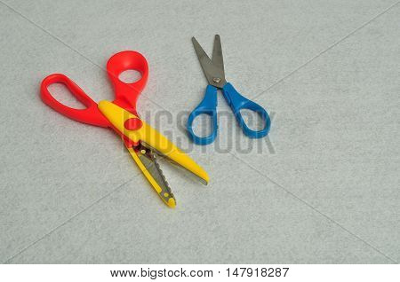 Colorful zig zag scissors isolated against a lined notebook page