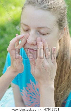 Portrait of a blond girl having applied makeup by a makeup artist in a park outdoors