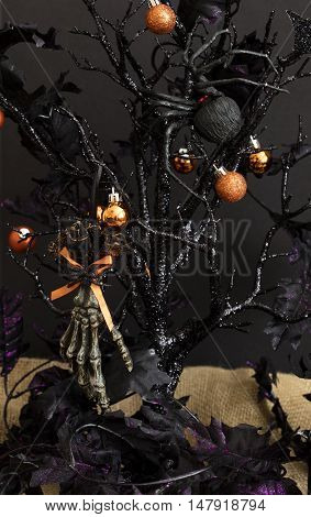 Black glittered Halloween tree with orange and black globes black widow and skeleton hand