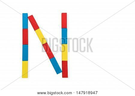 Capital letter N made up of different color wooden rectangular blocks isolated on a white background