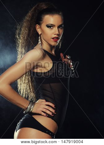 Fashion shoot of young sexy striptease dancer over dark background