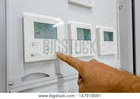 Hand is pushing button operating to climate control panel which contains a digital display for temperature check to residential place.