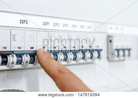 Hand finger is pushing for activation or shutdown automatic fuse breaker in modern control system at residential place.