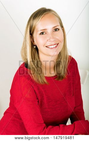 Studio shot of young blond woman wearing red pullover