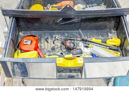 Variety of carpentry tools in tool box with open drawer on wooden floor.