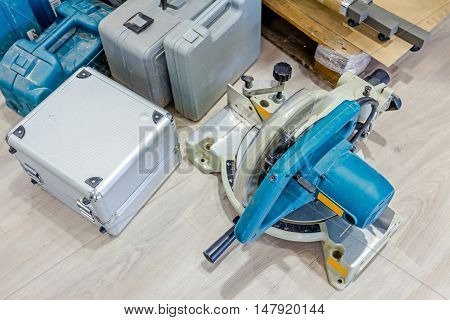 Various plastic tool boxes are on laminate floor with a lot of equipment for furnishing in workshop.