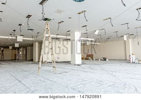 Workers are used wooden ladder to complete conditioning system ventilation at modern office ceiling with air duct and lamps.