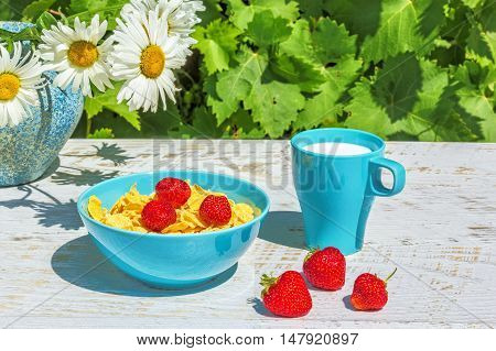 Breakfast in the garden on a sunny summer day. Bowl with corn flakes and strawberry mug with milk on a background white wooden table a bouquet of daisies and green grape leaves